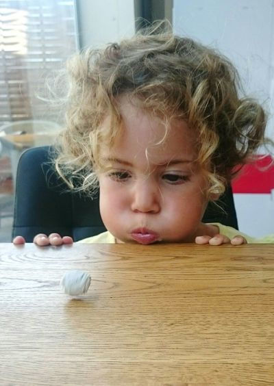 Close-Up Of Little Girl Blowing Crumpled Paper Ball On Table