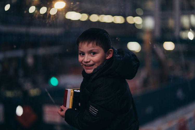 Portrait of smiling man holding drink at night
