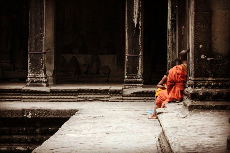 Monks sitting outside temple
