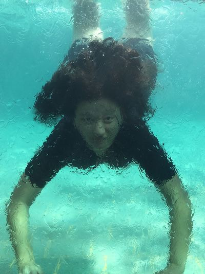 Portrait Of Woman Swimming Underwater In Pool