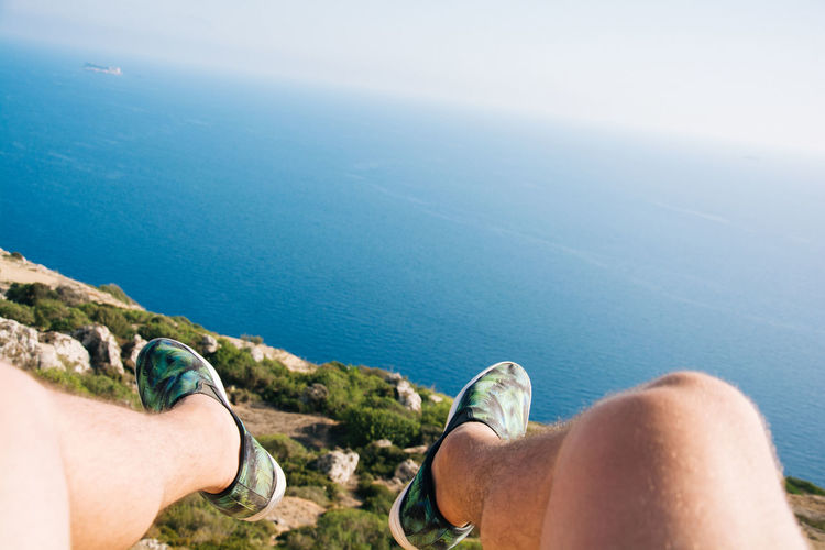 Low Section Of Man Dangling Legs Over Sea