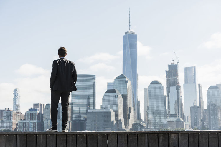 Rear view of man standing by buildings against sky
