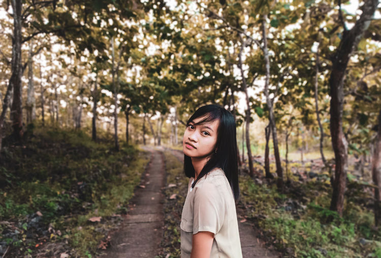 Portrait of beautiful young woman standing amidst trees in garden