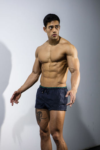 Muscular male fitness model posing behind a grey wall. Adult Asian  Athlete Body & Fitness Front Facing Human Body Long Shot Man Nam Vo Shirtless Sportsman Fitness Model Full Body Shot Grey Wall Handsome Hunk Looking Away From Camera Male Muscle Muscular Build One Person Strong Studio Shot Tatoo Torso