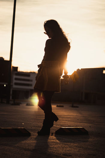 Side view of woman standing on street at sunset