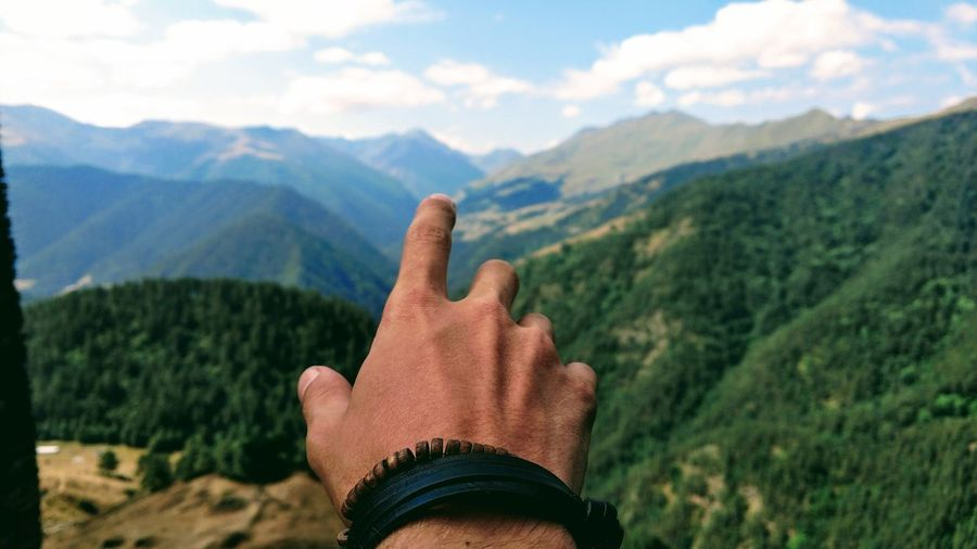 Cropped hand of man against mountain range