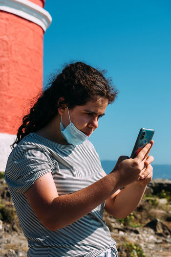 Young woman wearing face mask using mobile phone against sky