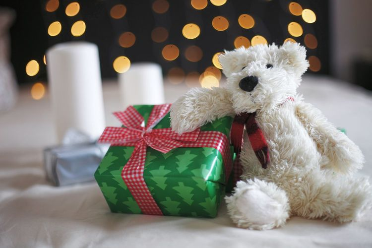 Close-up of christmas present with stuffed toy against illuminated lights