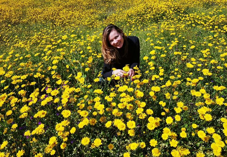 Portrait Of Woman Smiling Amidst Yellow Flowers On Field