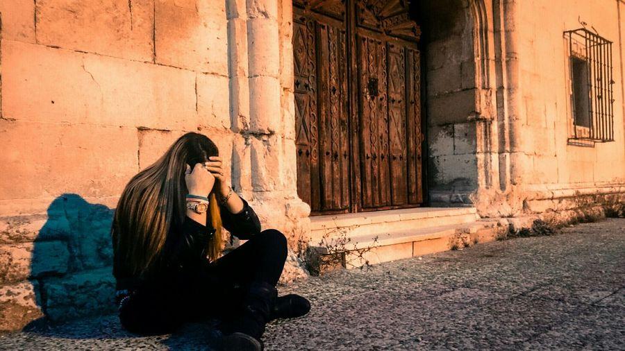 Depressed Woman Sitting On Sidewalk Against House In Town