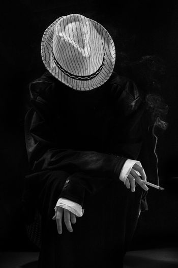 Rear view of person wearing hat standing against black background