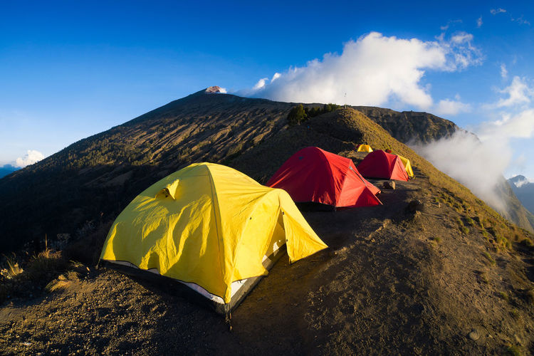 Tents on the rim of the mount Rinjani or Gunung Rinjani. The mount Rinjani is an active volcano in Indonesia on the island of Lombok. Panorama taken at sunset. ASIA Holidays INDONESIA Mount Rinjani Tourist Attraction  Background Photography Beauty In Nature Blue Sky Forest Golden Hour Hikers Landscape Lombok Mountain Mountain Range Outdoors Scenics Segara Anak Lake Sembalun Crater Rim Senaru Crater Rim Sunrise Sunset Tourist Destination