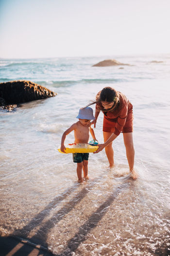 Mother and son with inflatable ring on beach