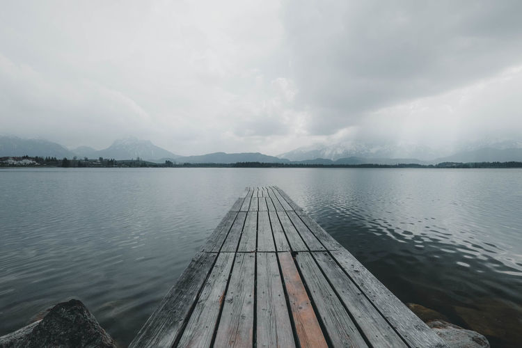 Footbridge leading into the water at lake hopfensee in the bavarian alps.