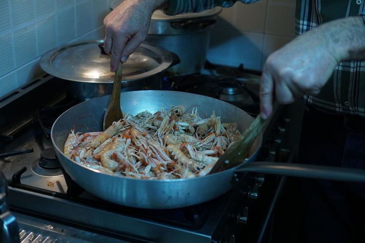 Midsection of man cooking shrimps in pan at kitchen
