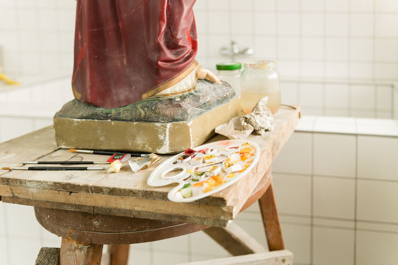 wooden desk with paint brushes and color palette used for restoration of a statue. Statue Close-up color palette Focus On Foreground No People Paint Brushes Preparation  Restoration In Progress Restoration Project Table Tiled Floor