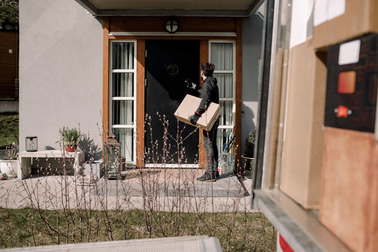 Man standing by window of house