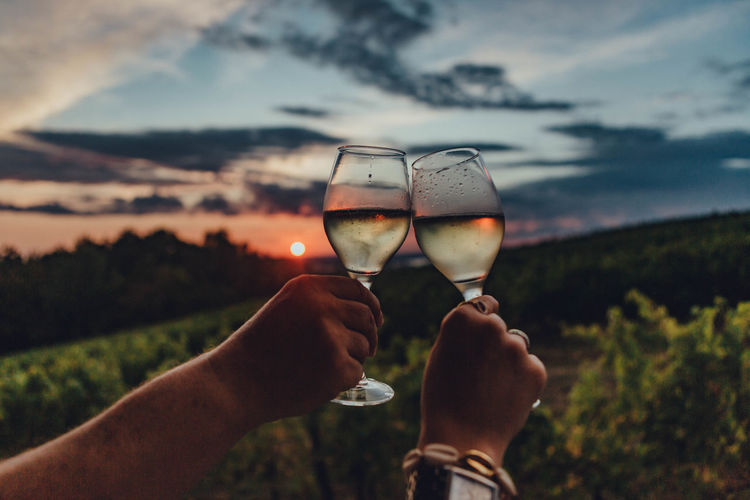 Midsection of man holding wineglass against sky during sunset