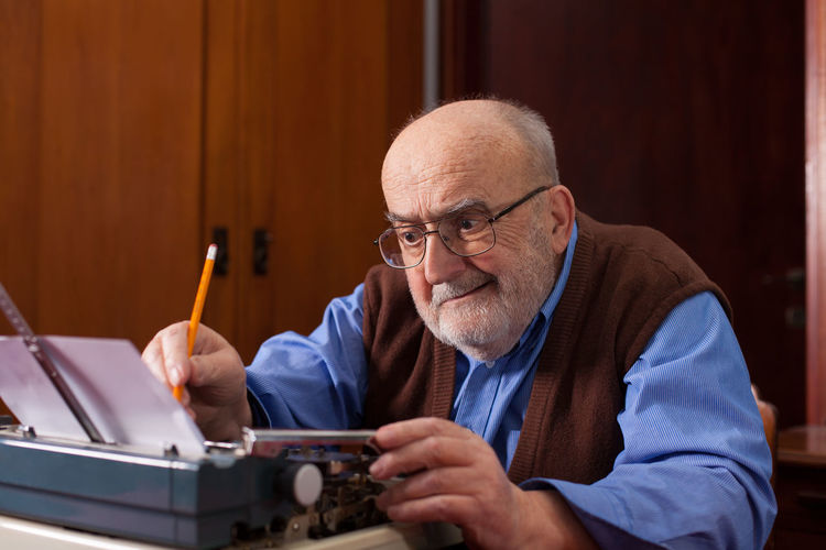 old man writing a novel Author Close-up Concentration Correcting Eyeglasses  Front View Indoors  Inspiration Letter Literature Machine Novel Paper Pencil People Retro Senior Men Sitting Story Table Typescript Typewriter Typing Wrinkled Writing