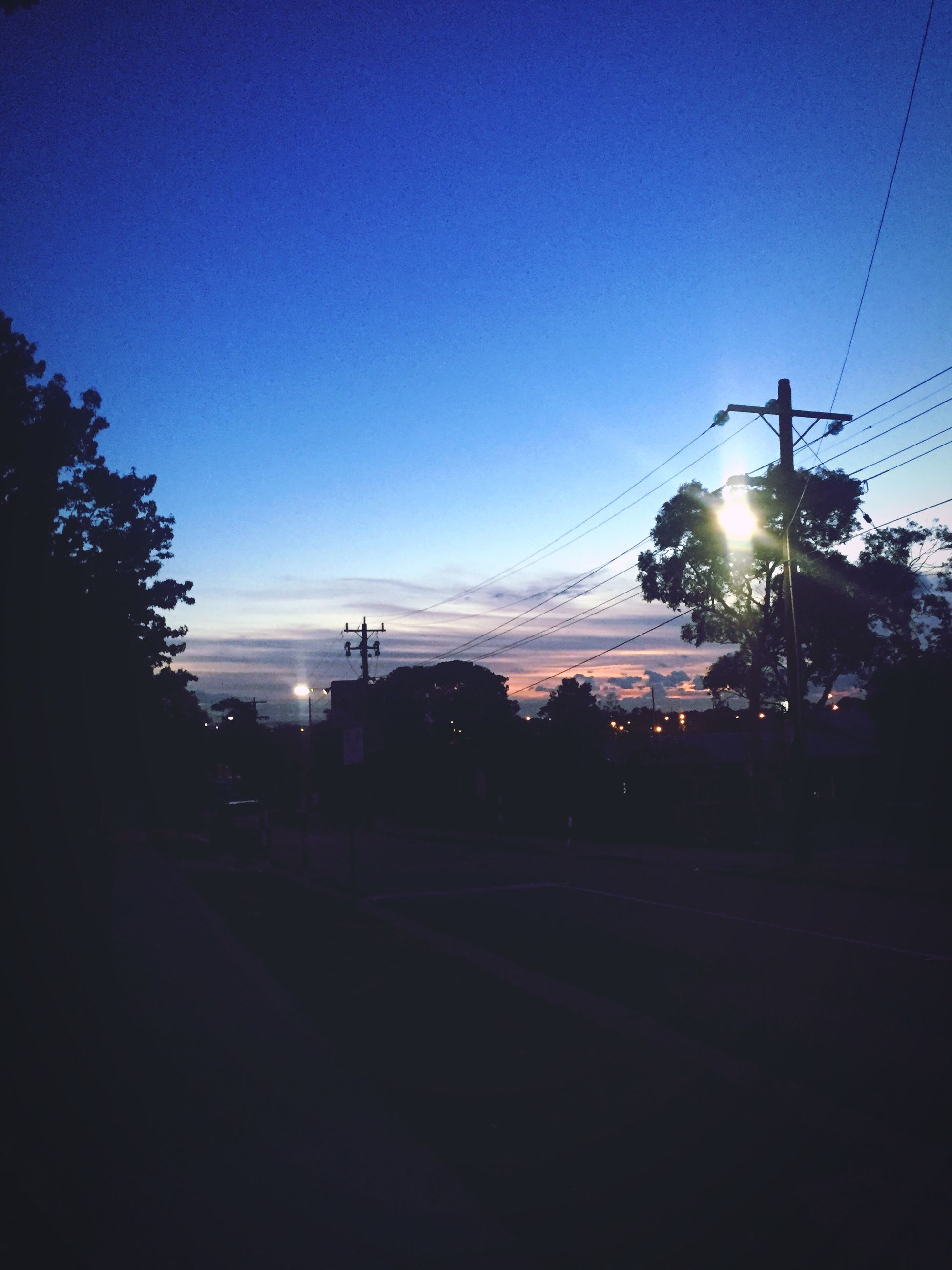 power line, silhouette, electricity pylon, clear sky, sunset, street light, tree, road, electricity, transportation, sky, sun, copy space, street, illuminated, blue, tranquility, power supply, dusk, nature