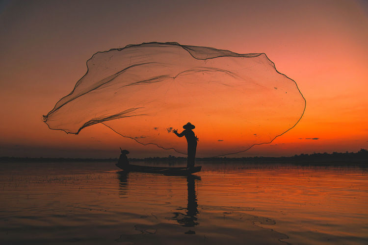 Fisherman tried to catch fish by throwing net fish in the Lake at the beginning of the day, Wanon niwat, Thailand. Country Way Of Life Beauty In Nature Fisherman Fishing Industry Idyllic Lake Landscape Lifestyles Men Nature One Person Orange Color Outdoors Real People Reflection Rural Life Rural Scene Scenics - Nature Silhouette Sky Standing Sunset Water Waterfront