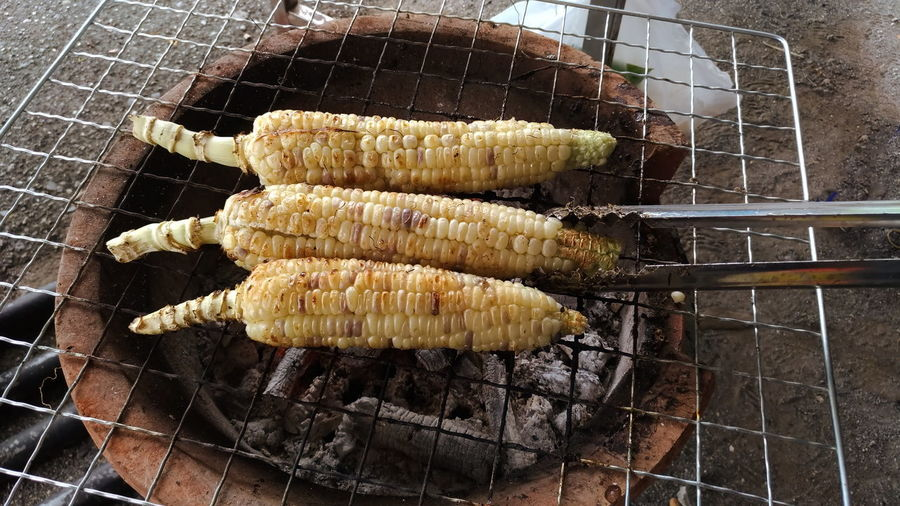 Are grilled corn on the grill in the fireplace. Grate Grill Grilled Corn Barbecue Barbecue Grill Close-up Corn Corn Stalks Day Fire Food Food And Drink Freshness Grate Grill Grilled Healthy Eating Heat - Temperature High Angle View Meat Preparation  Preparing Food Sweetcorn The Stove Vegetable Wellbeing