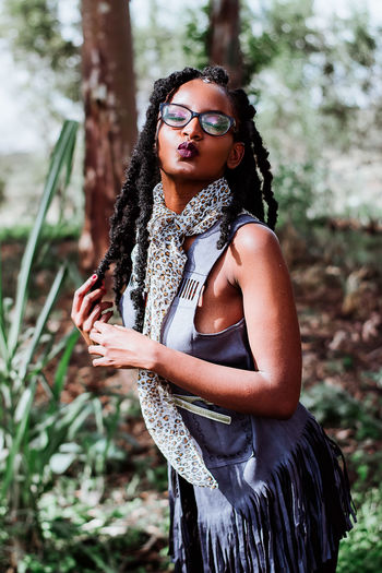 Portrait of young woman wearing eyeglasses standing against plants