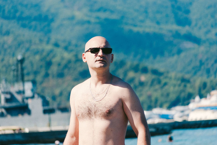 Shirtless bald man wearing sunglasses against mountain