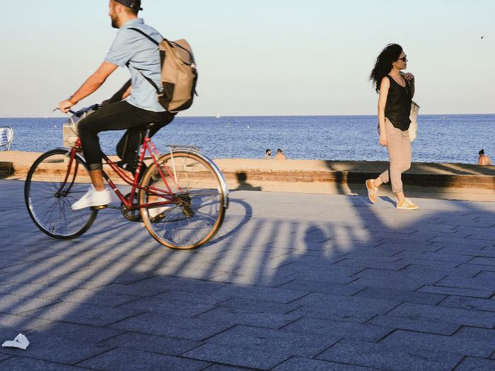Woman riding bicycle on street by sea against sky