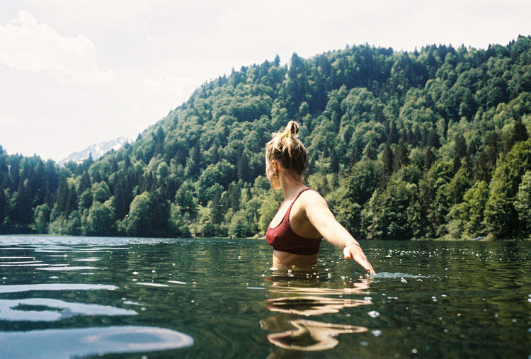 Woman standing in lake against trees