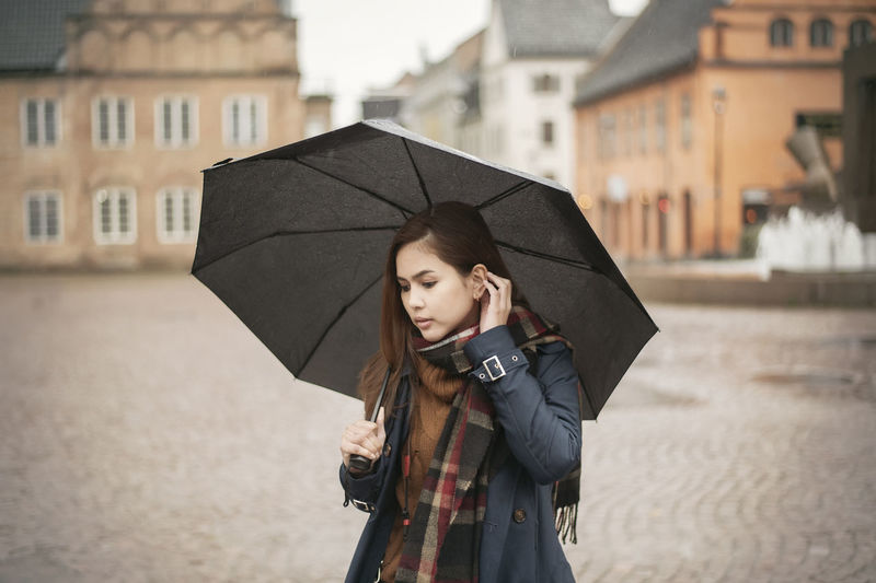 Thoughtful woman holding umbrella while standing in city during rain