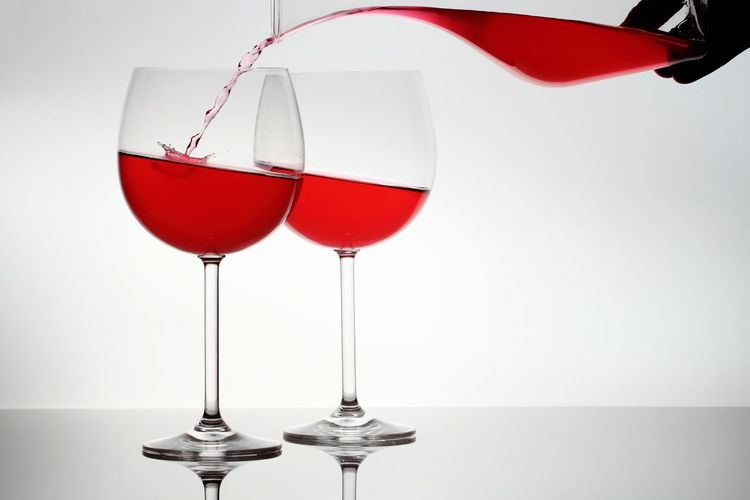 Close-up of wineglass on table against white background