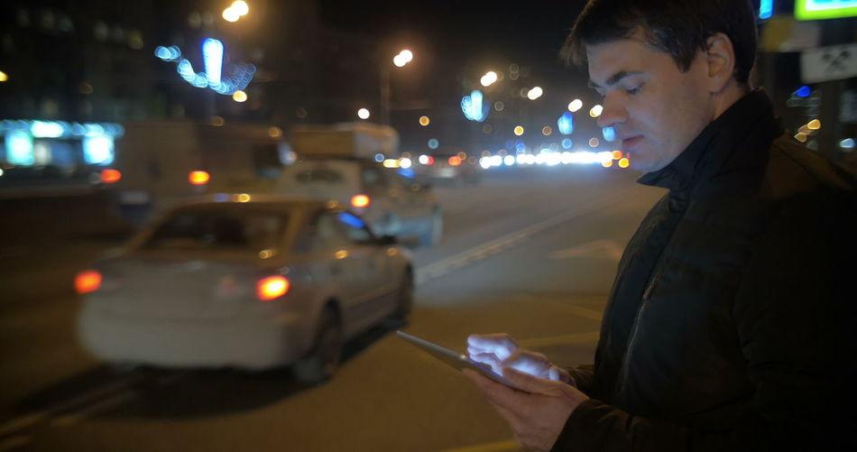 Man holding illuminated car on road at night