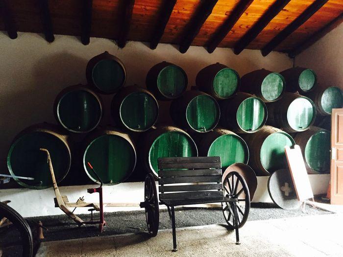 Empty chair against barrels indoors