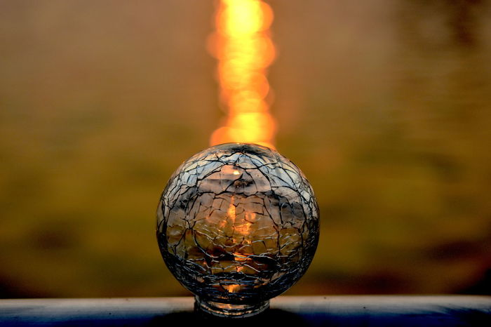 abstract, artistic, sun's rays reflection, Abstract Arts Close-up Cracked Glass Bulb With Sun's Rays Reflection On Lake Water Surface Day Focus On Foreground Imaginary Nature No People Outdoors