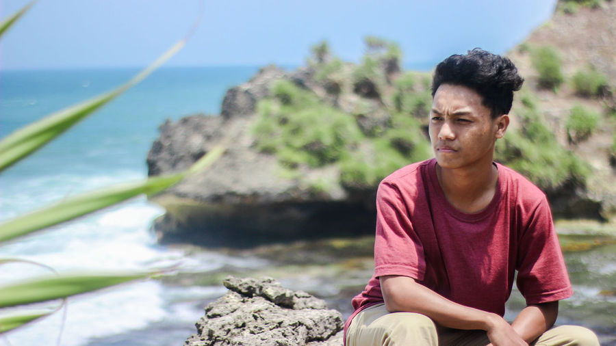 Young man sitting on rock by sea
