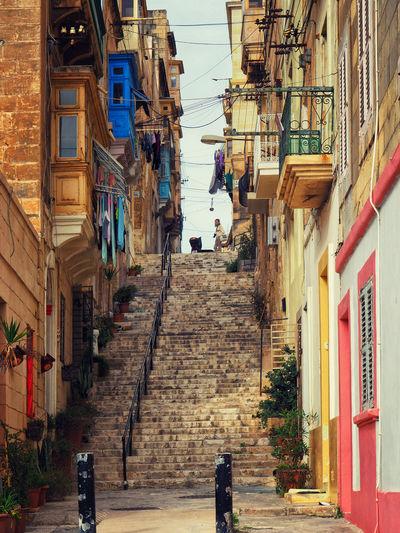 People walking on narrow alley amidst buildings