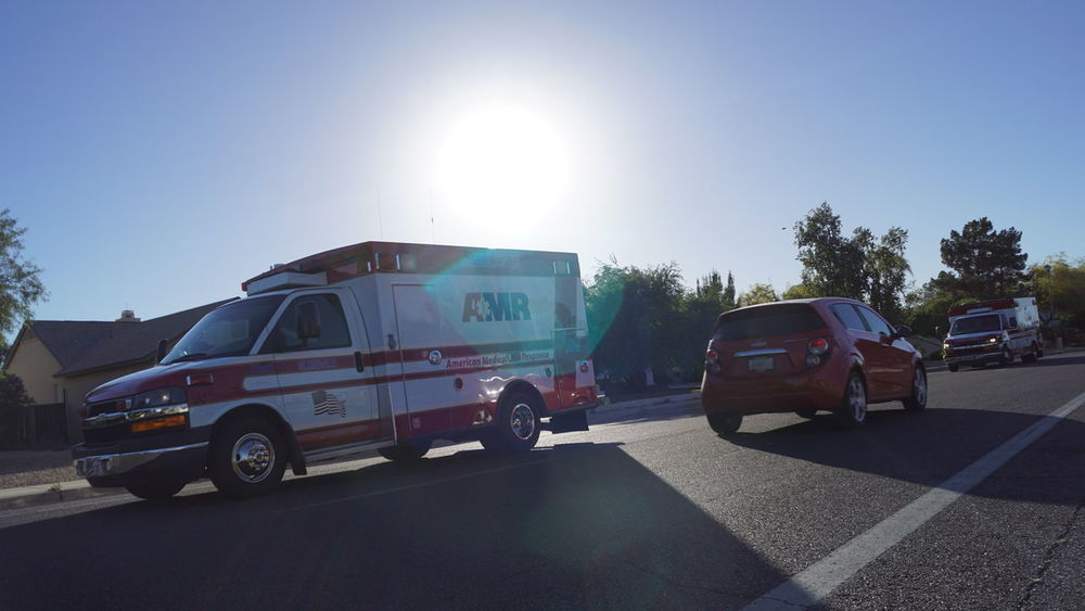 Ambulance American Medical Response Amr Architecture Car Clear Sky Day Fire Engine Land Vehicle Lens Flare Men Mode Of Transport Occupation One Person Outdoors People Real People Road Shadow Sky Sun Sunbeam Sunlight Sunny Transportation