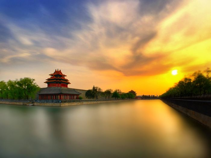 Traditional building by moat at forbidden city during sunset