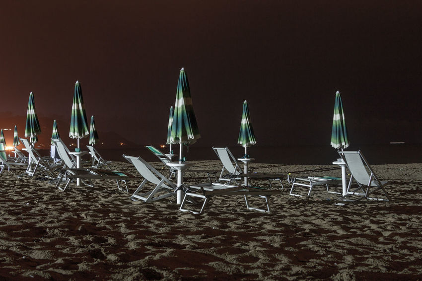 beach at night Abandoned Beach Beach Chairs Beachlife Coast Dark Loneliness Night Nightphotography No People Outdoors Sand Sea Shore Sun Shades Water Neon Life