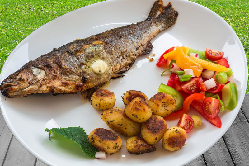 Roasted trout on white plate with lemon and roasted potatoes. Animal Waste Close-up Day Diet Fish Fish Food Food Food And Drink Freshness Freshwater Friends Garnished Healthy Eating High Angle View Indoors  Meat No People Plate Ready-to-eat Roasted Trout Serving Size Trout Meuniere