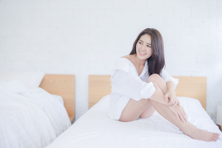 Beautiful Woman Sitting On Bed At Home