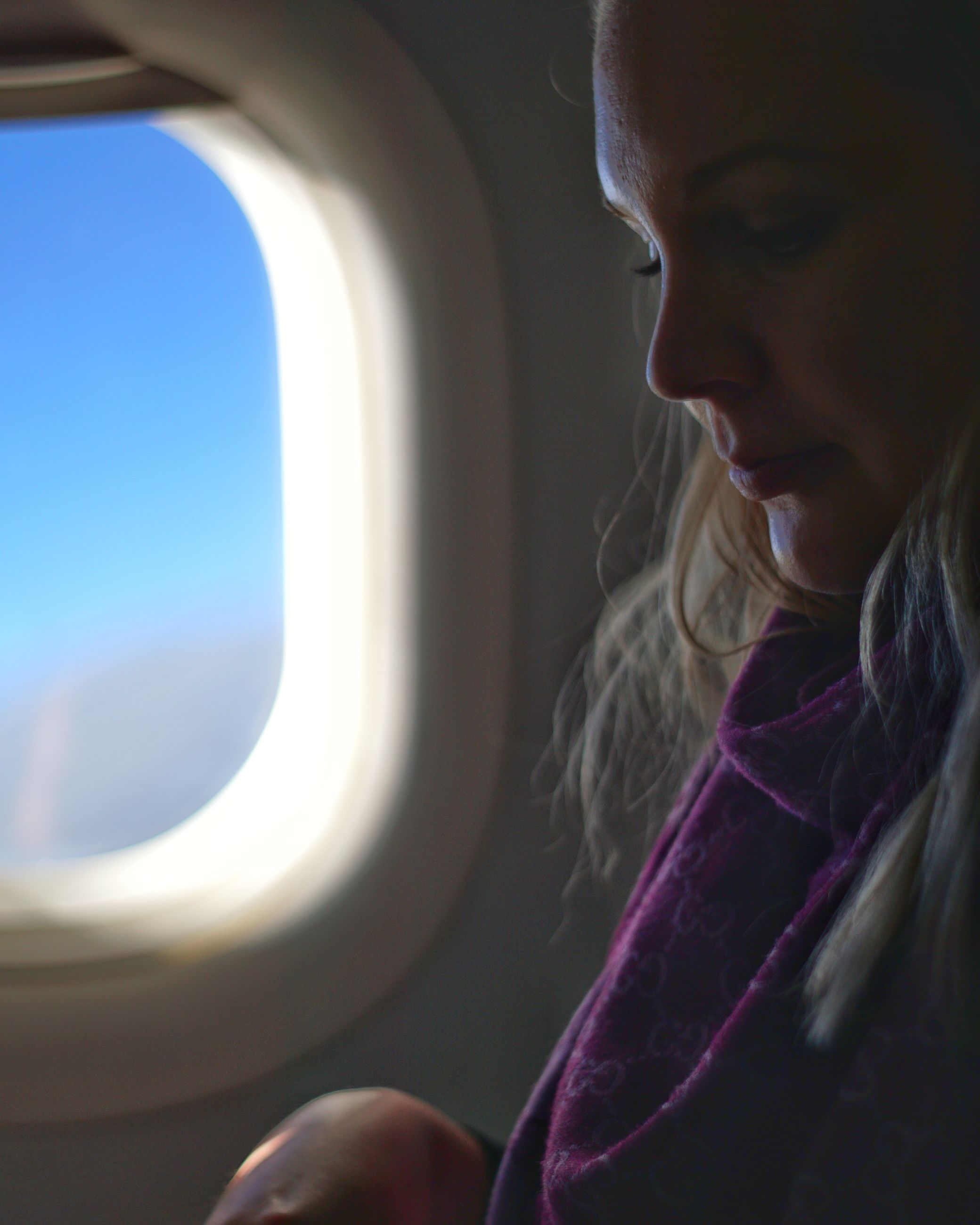 one person, window, looking, vehicle interior, real people, mode of transportation, lifestyles, headshot, air vehicle, young adult, travel, transportation, airplane, women, day, young women, sunlight, journey, outdoors, hairstyle