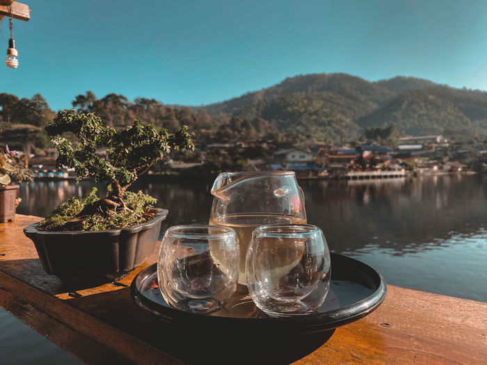 Drinking glass on table by lake against sky