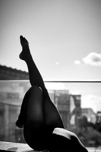 Low Section Of Seductive Woman Dancing On Building Terrace Against Sky