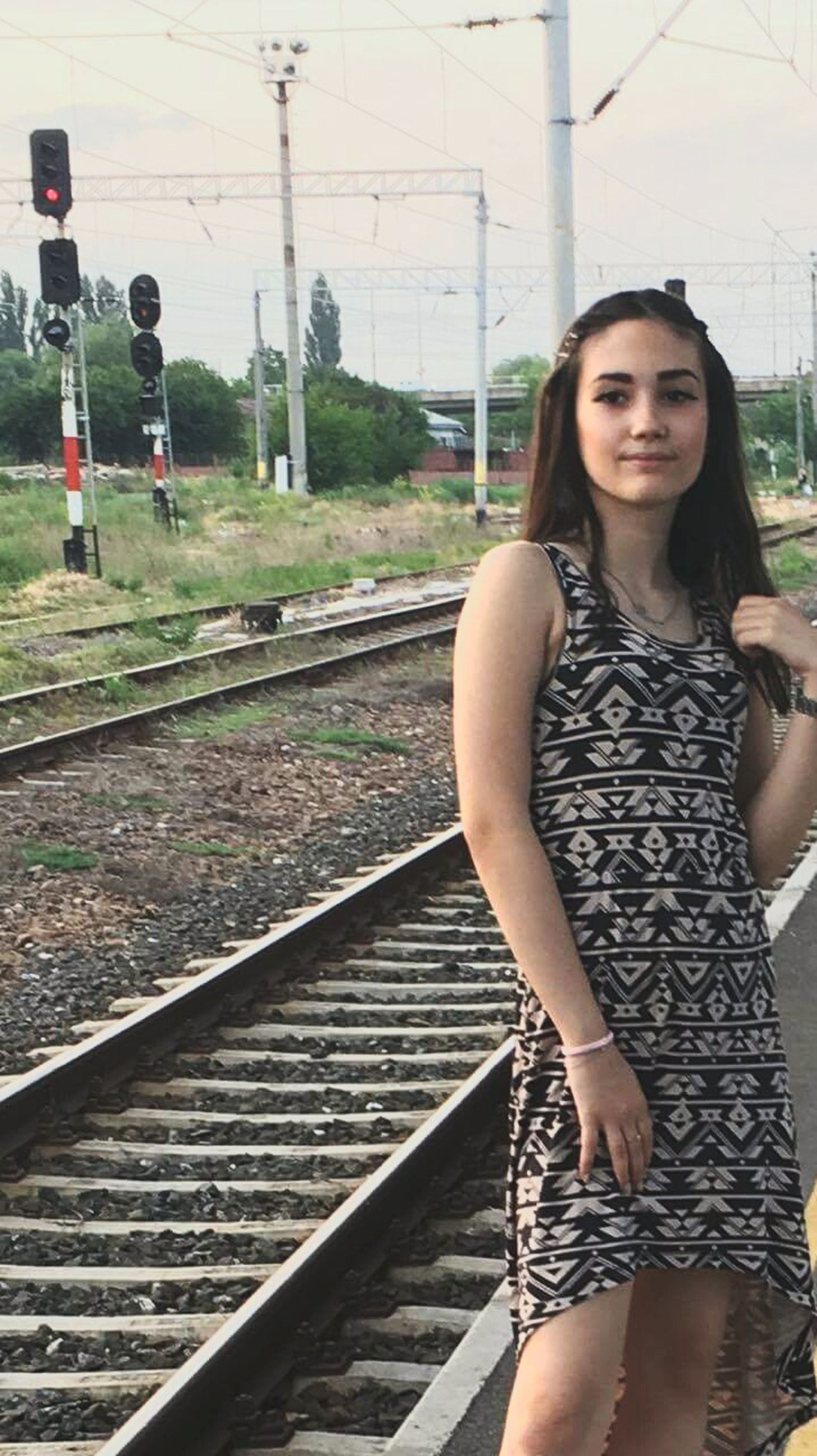 railroad track, one person, rail transportation, transportation, young adult, real people, young women, day, portrait, looking at camera, outdoors
