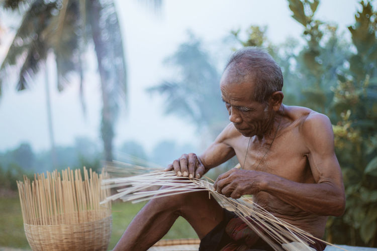 Shirtless man weaving wicker basket against trees
