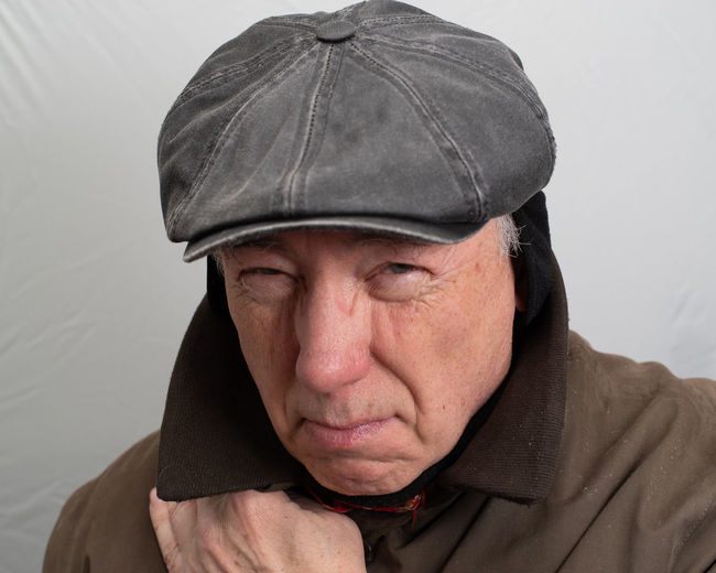 Close-up portrait of man wearing hat against wall