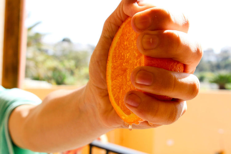 Close-Up Of Cropped Hand Squeezing Orange