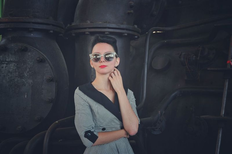 Young woman wearing sunglasses standing against machinery at factory